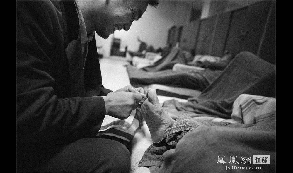 """惠金龙(左)帮客人修脚。惠金龙在这工作27年,去年还获得全国修脚师三等奖,在这里被称为""""修脚大师""""。(智德商旅--黄埔7号影像俱乐部/图 胥大伟/文)"""