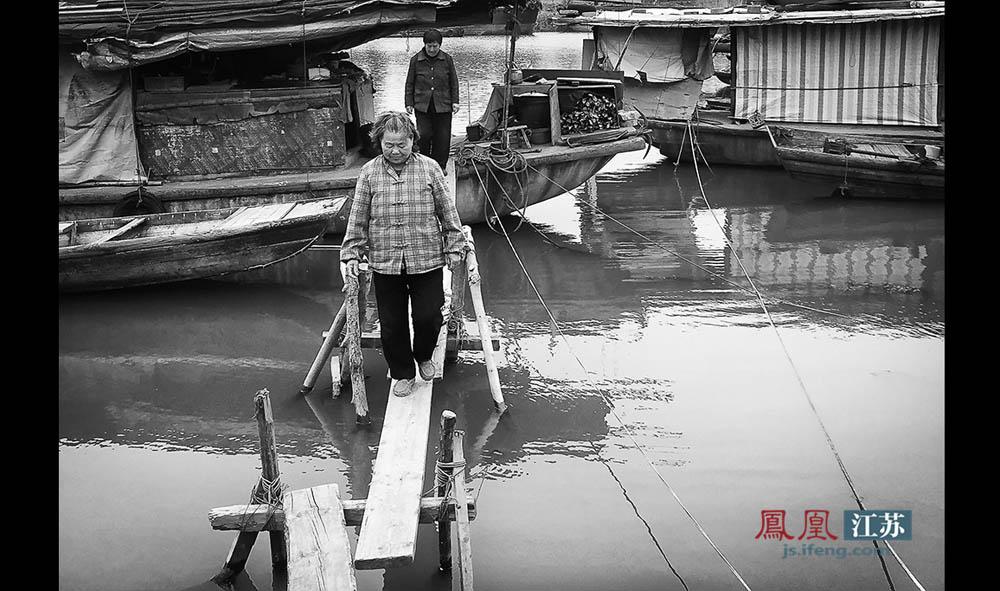 """连接渔船与河岸的是几块窄木板拼成的""""独木桥""""。每当下雨下雪,这些木板就会又湿又滑。对于上了年纪的老渔民来说,过""""独木桥""""就成了一件非常危险的事情,渔民们也大多会选择在船上呆着。(林琨/摄 胥大伟/文)"""