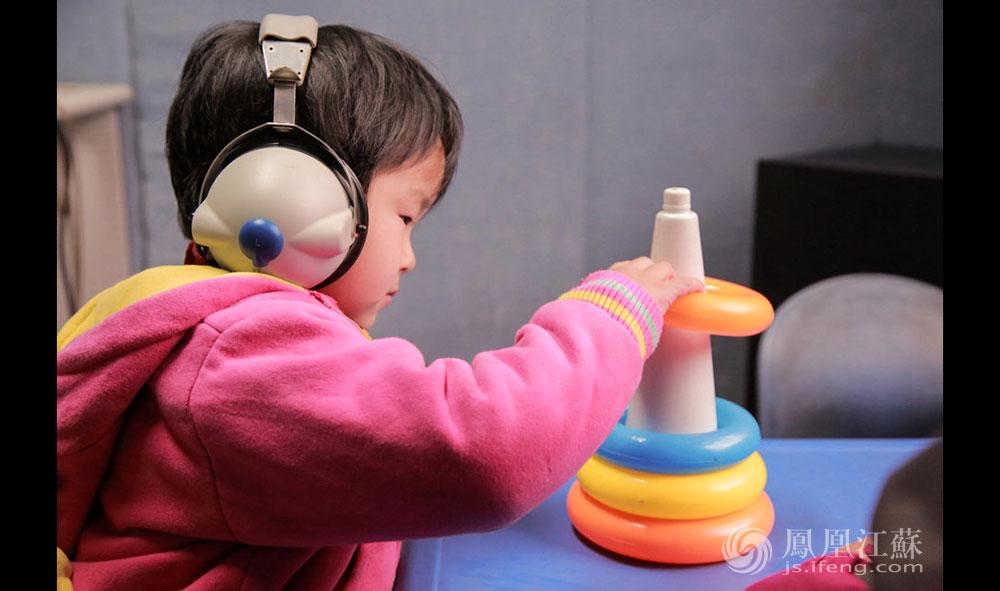 """下午,小雨(化名)在听力室里做听力测试。据测试的高老师介绍,所谓听力测试,就是让孩子在不戴助听器的情况下""""裸测"""",他打了个比方:""""就好比我们不戴眼镜测视力。""""按照要求,小雨在耳机里听到声音,就会将塑料圈套进白色的柱子内。有几次,仪器已经调到了105分贝,耳机里的声音大到让正常人很不舒服,然而小雨却没有反应。据了解,喷气式飞机起飞时的声音,也只有110分贝左右。(胥大伟 徐然/文 毛寿皓/图)"""