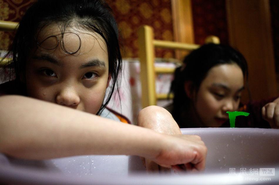 水帮她俩洗脚.刷牙洗脸她们可以自己完成. /摄 版   -男子筹钱为脑