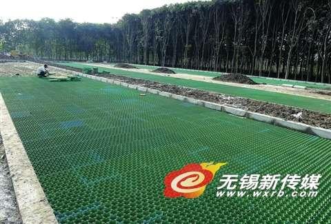 无锡 无锡生活  10月12日,工人在给生态湿地设立的停车位铺设植草格.
