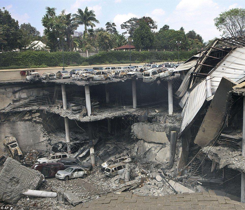 据英国《每日邮报》报道,9月23日,发生恐怖袭击事件的内罗毕Westgate购物中心传出猛烈爆炸声,购物中心顶层中部的停车场坍塌,压垮二层楼面。坍塌部分砸到地面,压到至少8名平民和1名袭击者。图为Westgate购物中心顶部停车场坍塌。