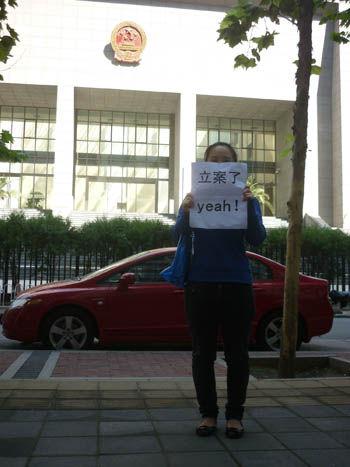 """曹菊(化名)到北京市海淀区法院交纳立案费,并手持""""立案了,yeah""""字板在法院门口拍照留念。"""