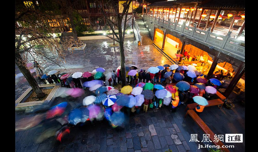 寺院内市民打伞排队等候,基本是中老年人,年轻人因为要上班,来得很少。去年,有一千多人进毗卢寺领粥。(黄埔7号影像俱乐部/图 胥大伟/文)