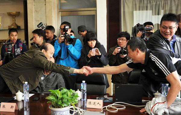 胡进(左)与刘长城握手。