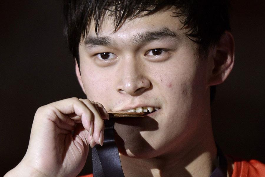 北京时间8月5日凌晨,西班牙巴塞罗那举行的2013年世界游泳锦标赛游泳项目进入最终日的争夺。在男子1500米自由泳的决赛中,孙杨力压群雄,以14分41秒15的成绩轻松完成卫冕。孙杨成功复制了澳大利亚自由泳之王哈克特在一届世锦赛中包揽这三个项目的神迹。此外,孙杨荣膺世游赛最佳男运动员,这是中国乃至亚洲运动员的首次。图为孙杨在颁奖仪式上。