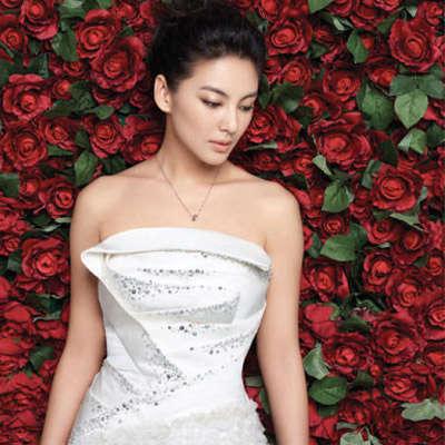 张雨绮背靠红色玫瑰花墙,以简单干练的新娘盘发搭配抹胸婚纱亮相