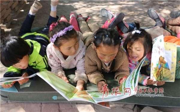 """资料图 青岛日报/青报网讯""""这个故事真好玩!""""""""我最喜欢这个小动物了!""""""""老师,燕子冬天为什么南飞?""""不大的校园里传来阵阵欢笑声,正在看绘本图书的是甘肃省甘南化旦尖措孤儿学校的学生,这是他们第一次接触绘本图书,连续几天,他们都来到手拉手""""阅来悦有样""""绘本角,阅读这些图书。 这些绘本图书是青岛农业大学手拉手义务支教队甘肃小分队的大学生们带来的,除了农业大学学生郭广增等自己手绘的几本图书外,他们还购买了部分绘本图"""