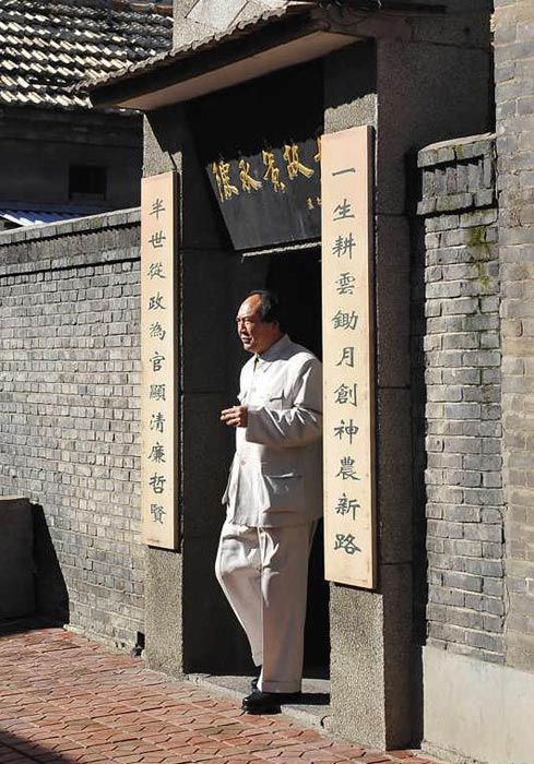 大寨位于山西省昔阳县,解放前,这里穷山恶水,七沟八梁一面坡,自然环境恶劣,群众生活十分艰苦。图为一名毛泽东扮演者从陈永贵故居走出。(图片来源:凤凰网历史)