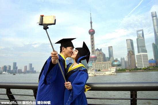 一对学生情侣穿硕士服自拍 2015年5月17日,上海,记者在外滩采风时,遇见一对穿着硕士服高高兴兴的相依在一起在自拍留影。他们分别来自山东和江苏,于2012年考上上海电力学院,是学校的研究生。他们是在学校中通过校园活动认识的。今年要毕业了,前段时间一起签约了杭州的公司,可是近期内还有上海其他的单位和他们联系,所以工作的事情现在还在考虑。 看着天气比较好,另外周一学校的硕士服就要上交,于是赶紧去了外滩拍照,也是给他们研究生生活画上一个圆满的句号。