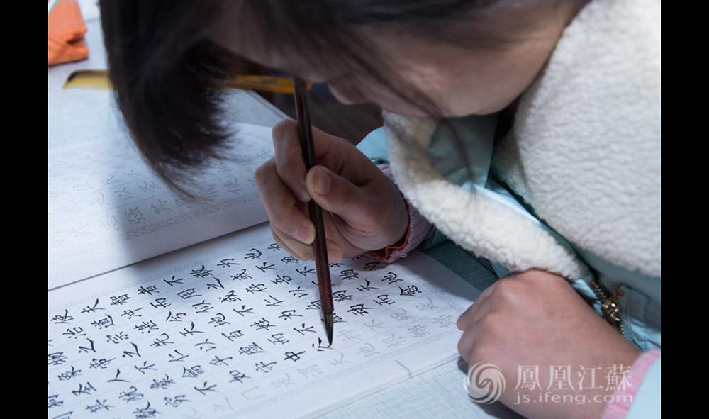 """王灿灿小时候学过书法,她至今都保留着写毛笔字的习惯,这也是她排解工作压力的方式之一。她说自己算是标准的技术宅,不喜欢出去玩,休息一般都是窝在家里。最近她在看《红楼梦》,她说自己最喜欢王熙凤的丫鬟平儿,""""我感觉她是小说里最善良的一个人。""""(汪霞/文 毛寿皓/摄)"""