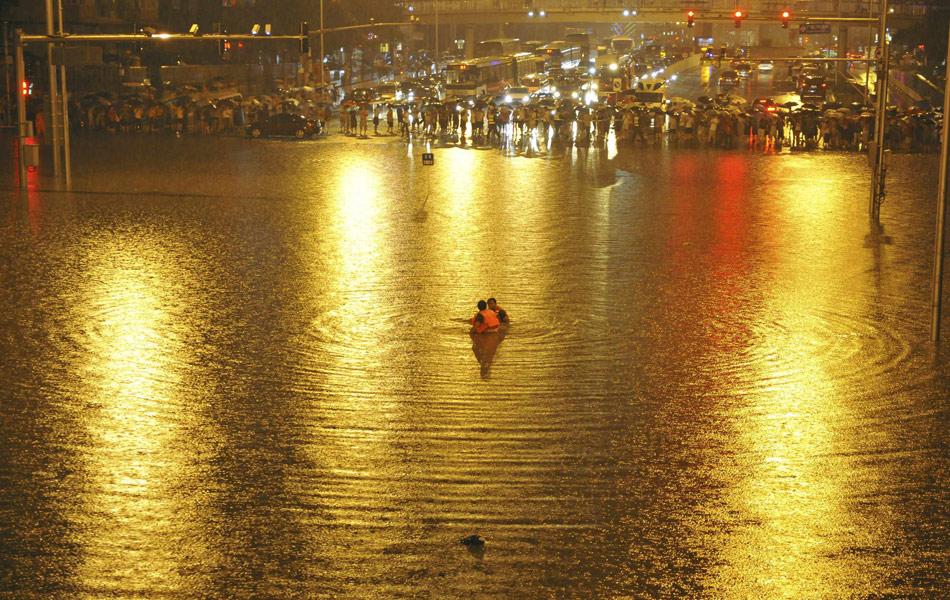 北京21日出现的强暴雨为61年来最大降水。暴雨使北京广渠门桥下一片汪洋,五辆车搁浅水中,其中一辆越野车中被困男子虽被救出,但送医抢救无效身亡。图为搜救人员。