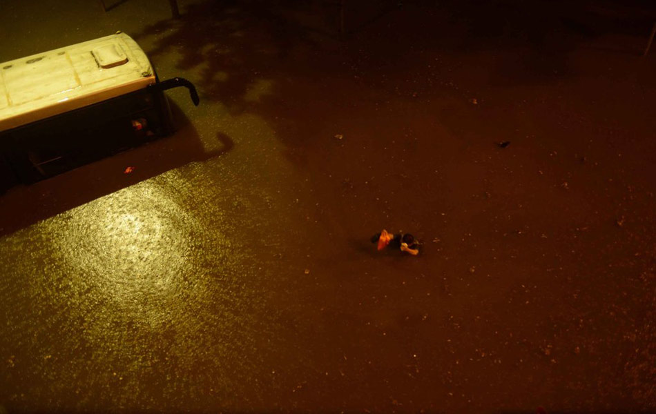 北京21日出现的强暴雨为61来年最大降水。大红门下的积水非常深,公交车趴窝了,水已经淹没到车窗,一个人手举着东西。