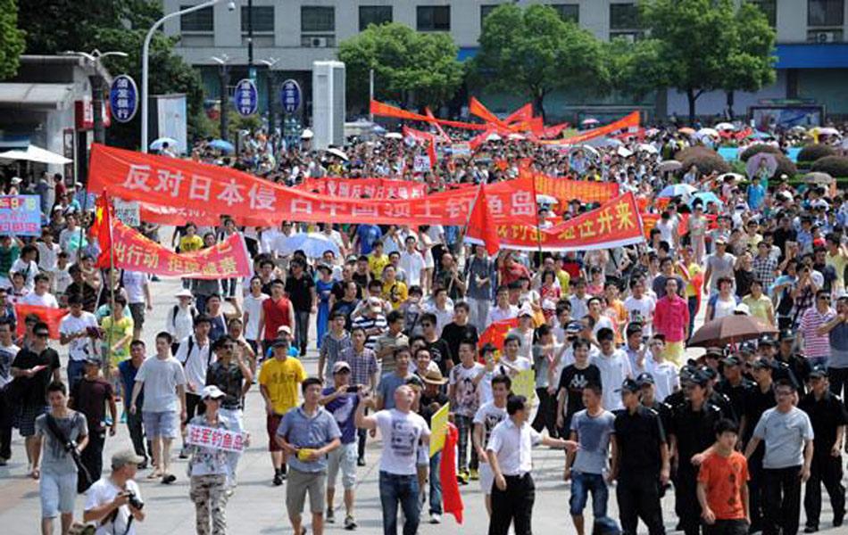"""新华社杭州8月19日电(记者张遥、方列、裘立华)19日上午,在杭州市主城区武林小广场发生规模不小的反日游行活动。截至记者发稿时,已有数百人参加到此活动中,游行队伍行进到环城西路浙江省委省政府附近。记者上午9时左右就在武林小广场周围发现有约百人围聚,其中包括儿童,儿童手中举着标语,四周有二三十人拿着小摄像机在摄像,旁边还有部分公安人员与警车。此后,不断有围观者陆续加入,横幅有十几条,还有的横幅上印着钓鱼岛的图片。半小时后,聚集的人群开始沿着武林小广场出发往街路上行进,队伍十分整齐,每排有七八个人。有带着人喊着""""抵制日货""""""""还我钓鱼岛""""等口号,后面队伍越来越长。记者注意到,在队伍的首尾处均有公安人员跟着,但没有与游行者发生冲突。有的游行者的传单上写着一些话,大意为""""我们保卫钓鱼岛是爱国行为,请警察支持爱国行为""""。队伍以20-30岁的年轻人为主,其中有不少是学生模样。图为杭州反日集会。"""