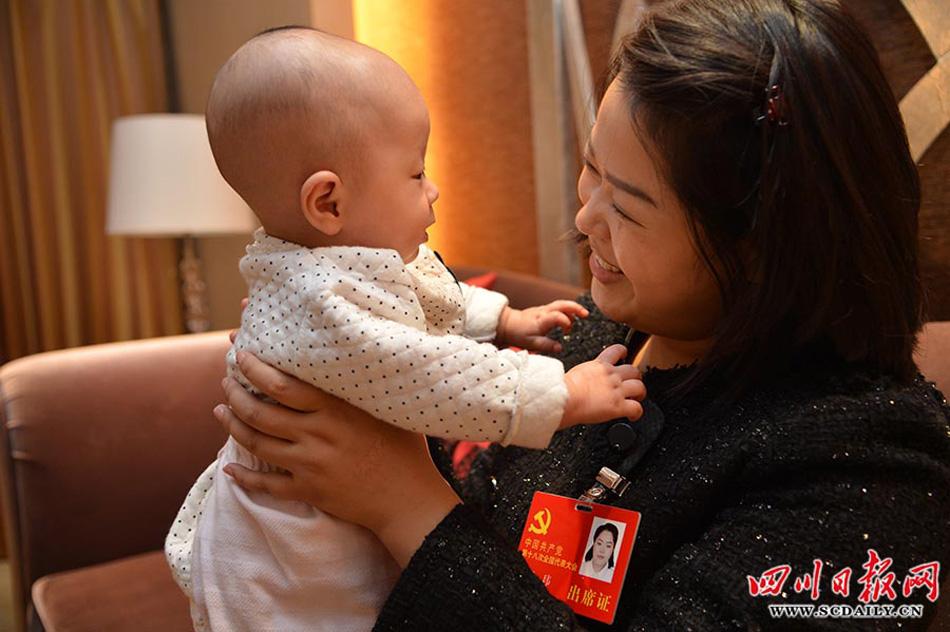 2012年11月10日晚,北京,四川省代表团驻地。四川省出席党的十八大代表中最年轻的代表罗玮参加完四川团的会议,回到驻地房间继续阅读学习大会的有关材料,把已有睡意的女儿斜抱在怀中。