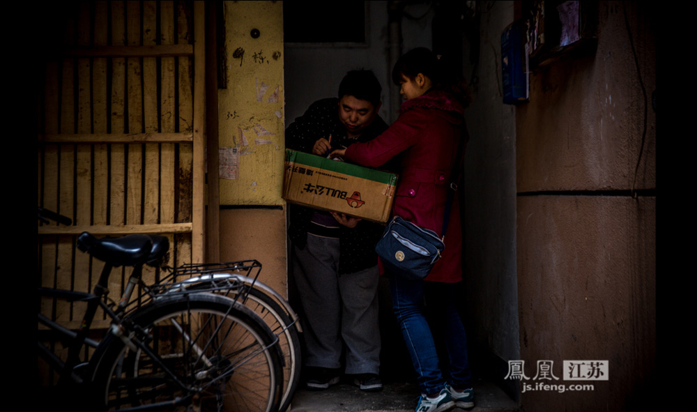 """快递员的工作,让小李在这两年从腼腆的农妇迅速变成了天不怕地不怕的""""女汉子"""",一口气爬五六趟六层楼来回送货上门是常事,她笑称自己是专业级的爬楼健将,""""有些男人都不如我""""。(彭铭/摄 孙鸣柳/文)"""