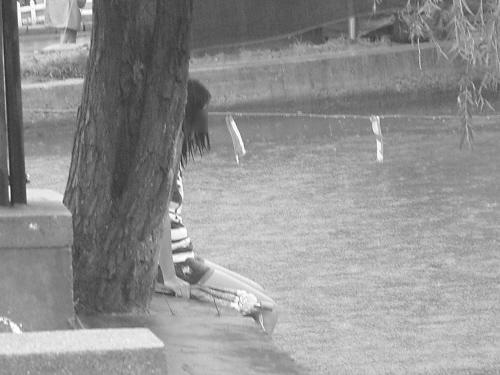 女子呆坐湖边,全身都被淋湿.图片