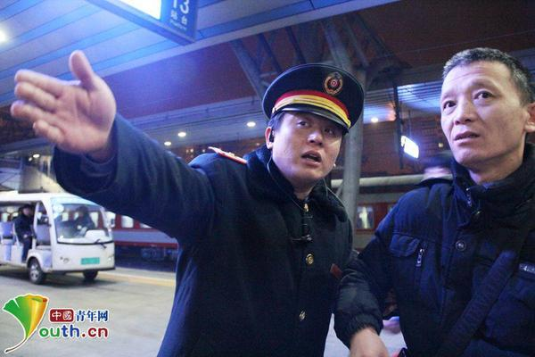 K95次列车列车长金浩在站台上为旅客排忧解难。中国青年网记者刘洪侠 摄