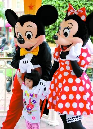 """香港迪士尼乐园,一位小朋友与卡通人物""""米奇"""",""""米妮""""合影.新华社 发"""
