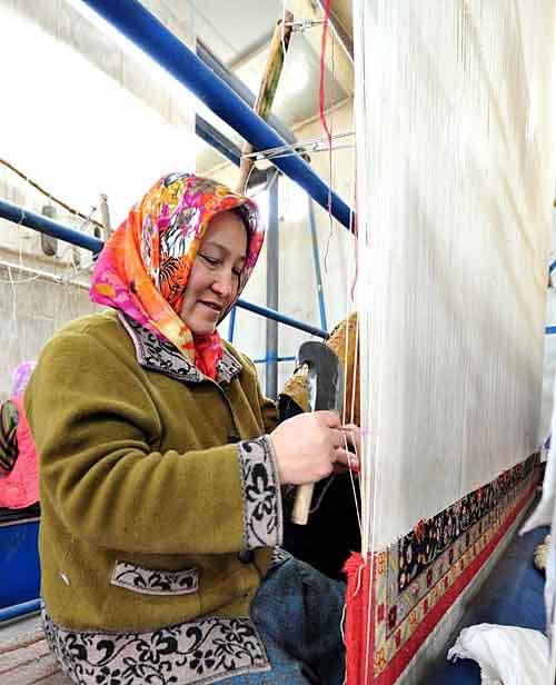 努尔丽莎在熟练地编织地毯
