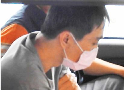 杀害前妻的李姓男子坐上警车低头沉默不语。来源:台湾《联合报》