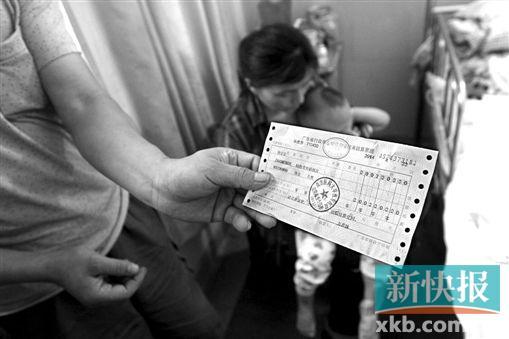 ■巨额的住院费用让小轩的家属无法承受。图中小轩爷爷手中拿着的是身上最后的2000块钱费用票据。    新快报记者祝贺/摄