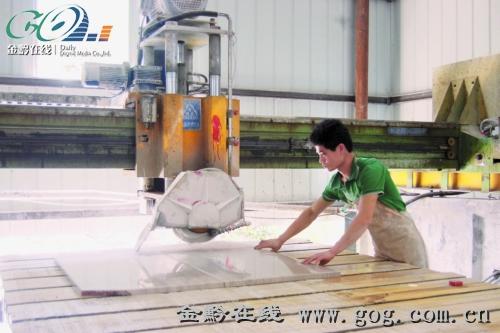 图为工人操作红外线切割机加工规格板
