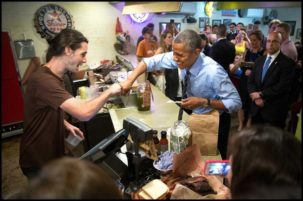 奥巴马在富兰克林烧烤店付钱时与收银员碰拳。(资料图片)