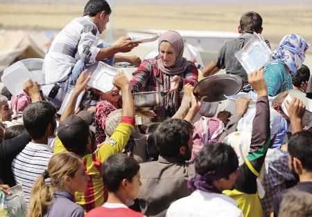 8月14日,在叙利亚东北部的难民营,伊拉克雅兹迪教徒在领取食物.