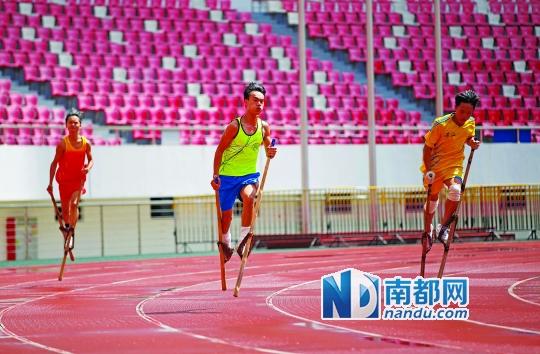 脚竞速赛场上,运动员踩着高脚在跑道上奔跑.-有一种飞人踩在竹竿