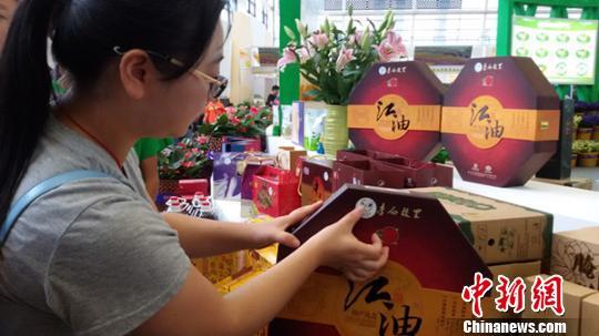 图为现场工作人员正在为商品贴上统一的地域商标LOGO 董媛媛摄
