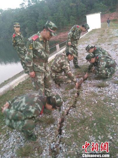 图为官兵们查看坝体上的裂缝。 李斌摄