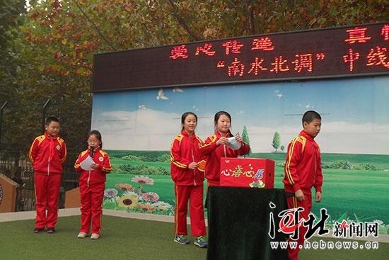 天苑小学的学生代表将自己制作的祝福卡放到心愿箱中