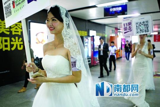 """3 """"光棍节""""当天,一群身穿婚纱的美女在深圳大剧院站内快闪求抱走。"""