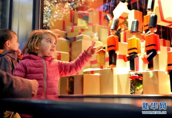 11月27日,一名儿童在法国巴黎春天百货公司橱窗前观看配乐木偶玩具