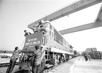 """工作人员为首班开行的""""义新欧""""国际货运列车挂上标牌。新华社记者 徐 昱摄"""