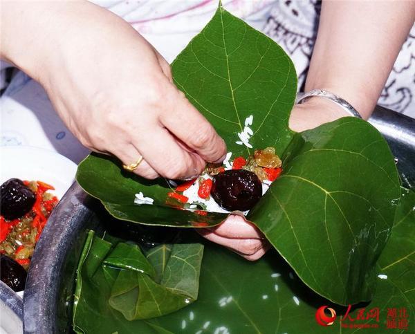通常是先将粽子叶蒸一下,然后用凉水漂一下,漂好后折成窝放入一些糯米