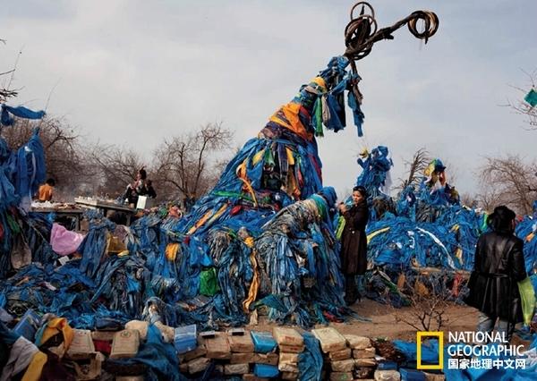 """这棵象征永恒的""""母亲树""""是位于蒙古北部的一棵松树,吸引着来自四面八方的朝圣者。层层叠叠的织物祭品已将它压垮。蓝色织品象征着永恒的天国与宁静。"""