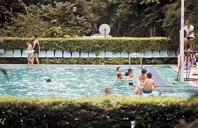 7日,渝北某小区,市民在泳池游泳。 重庆晨报记者 雷键 摄