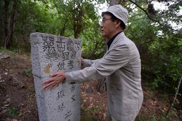 8月10日,在黑龙江省牡丹江市,中岛幼八见到养父母的墓激动不已.