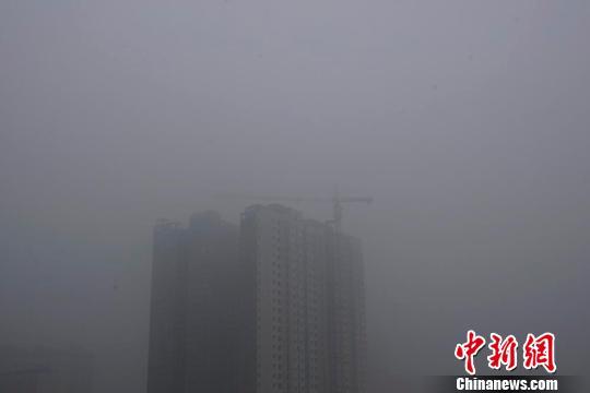 12月4日,新疆乌鲁木齐市中心城区被雾霾所笼罩,街道两旁的楼宇淹没在