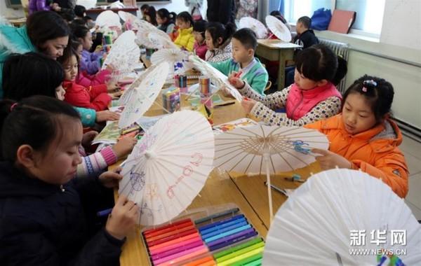 2016年1月23日,北京市东城区少年宫第二届春节儿童书画室内庙会举行,小学生们在这里可以体验做彩伞、画灯笼、剪窗花、写对联等传统民俗,还可以参加跳房子、滚铁环等游戏,感受传统文化魅力。新华社发(周良摄)