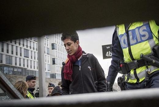 2015年11月12日,在瑞典马尔默市,边防警察将一名非法移民带下火车。(图片来源:新华社)