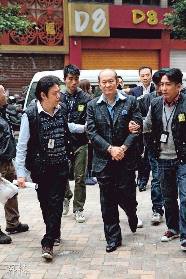 资料图片:2015年何献伦(中)被押往澳门检察院时的情景。