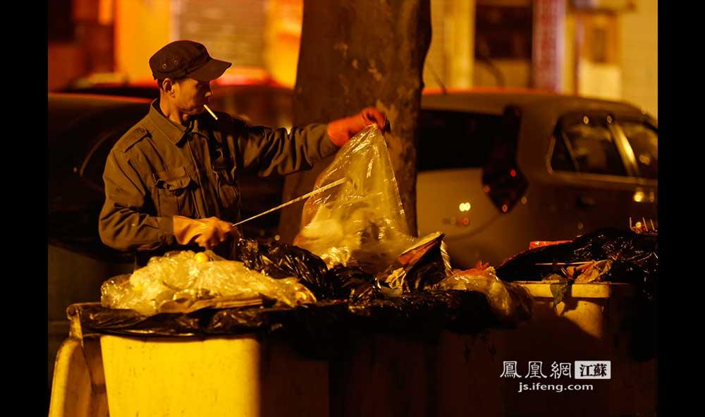 11月17日0:44,鼓楼区汉口路,63岁的赵大爷在翻捡垃圾。赵大爷说他白天看自行车、电动车,天黑了就骑三轮车出来捡垃圾卖钱补贴家用,一般要到凌晨两三点钟才收工回家。(王剑/摄)