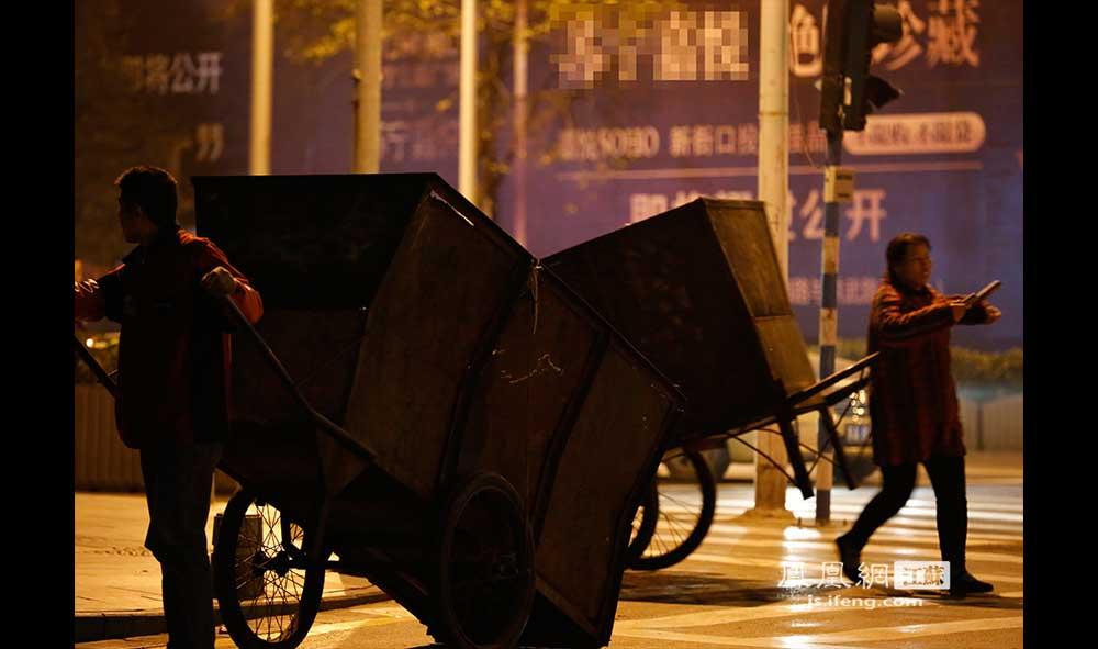 11月16日0:28,新街口淮海路,两名清洁工人拖着垃圾车停下来交谈。(王剑/摄)