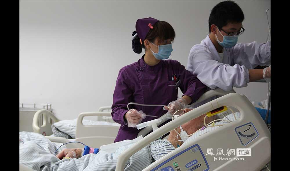 11月18日23:42,江苏省中西医结合医院急诊重症监护室,医护人员为一位老年患者吸痰。医护工作每天三班倒,小夜班下午5点到午夜12点,大夜班午夜12点到早上8点。近些年医患关系紧张,医护人员也非常不容易。(王剑/摄)