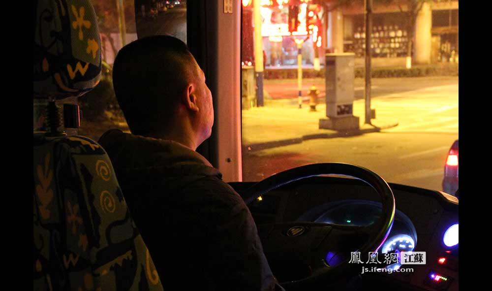11月16日3:50,吕师傅驾驶W801路夜间公交车行驶在马路上。吕师傅干这行4年多,每晚10点到早上7点。尽管开夜班一个月要比开白班少几百块钱,但因为白天需要照顾家中老人,吕师傅还是当了一名夜班公交车司机。(王剑/摄)