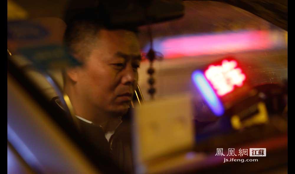 11月16日1:40,秦淮区长乐路一家KTV门口,出租车司机徐师傅坐在车里等客。(王剑/摄)