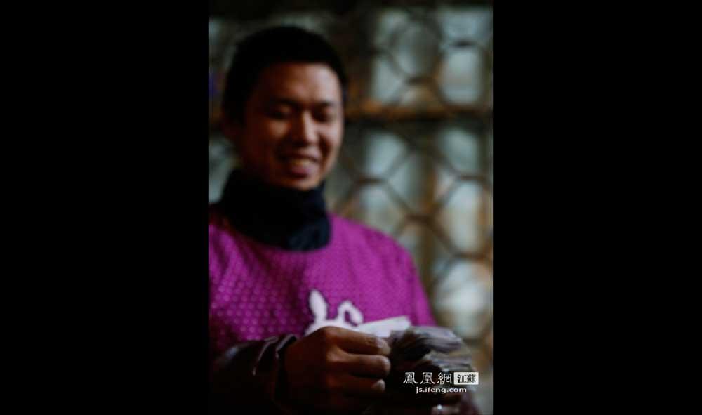 11月16日1:57,秦淮区长乐路,卖猪蹄的方师傅数着一晚上赚的钱,露出笑容。他一般每天清晨5点起床煮猪蹄,第二天凌晨2:30左右收摊。(王剑/摄)